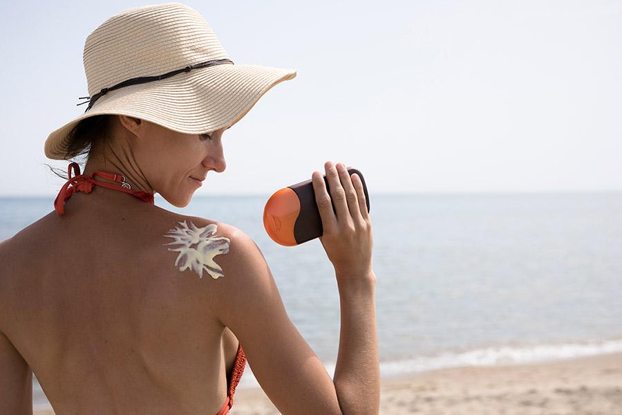 mujer en la playa con protección solar y sombrero